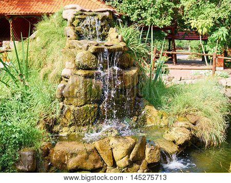 Beautiful waterfall in garden in summer. Meditation relaxation and rest.