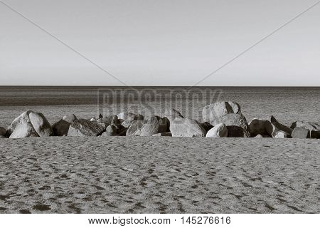 the sandy beach and big stones boulders ashore near water and the line of the horizon over water monochrome tone