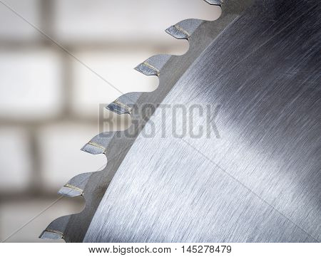 Disc circular saw close-up on a background of a brick wall.