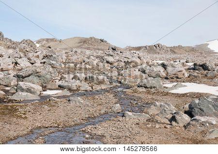 Rock mountains and snow melting at Antarctica