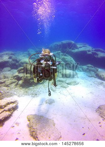 A young scuba diver lady swimming underwater. View of the scuba diver gear fins mask regulator bcd and bubbles maintaing buoyancy in the deep blue sea of Protaras Cyprus.