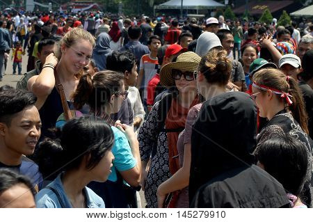 Jakarta, Indonesia - August 17, 2016: Group of women's spectators in the middle of crowd after independence day flag ceremonial at Indonesian Presidential Palace.