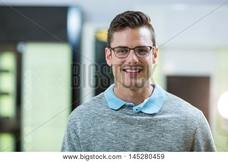 Portrait of smiling customer wearing spectacles in optical store