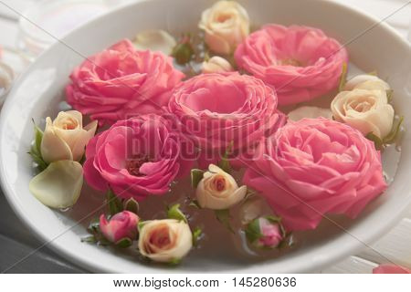 Bowl with roses in water closeup