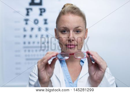 Beautiful female optometrist holding spectacles in ophthalmology clinic