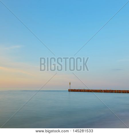 Sunset On The Beach With A Wooden Breakwater, Long Exposure