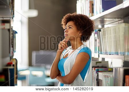 education, high school, university, learning and people concept - african american student girl choosing book at library