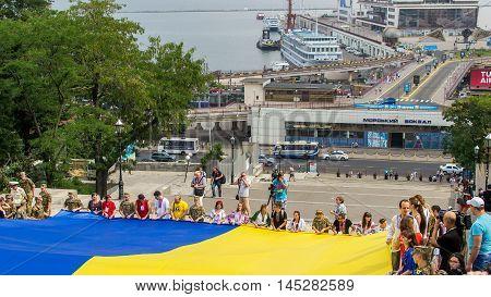Odessa Ukraine - August 23, 2016: National Flag Day celebration. Large Ukrainian flag on the background of the sea port.