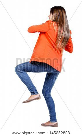 back view of woman funny fights waving his arms and legs. business woman in a red jacket kicks.
