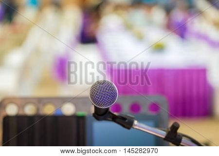Close up of microphone in concert hall or conference room background.