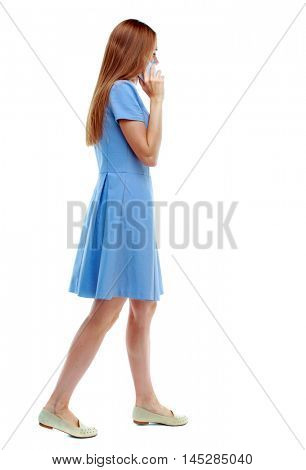 side view of a woman walking with a mobile phone. beautiful girl in motion. Isolated over white background. blonde in a blue dress while walking communicates the white smartphone.