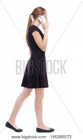 side view of a woman walking with a mobile phone. Rear view people collection. Isolated over white background. Blonde in a short black dress and is talking on the phone.