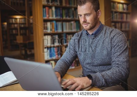 Mature student using laptop at college library