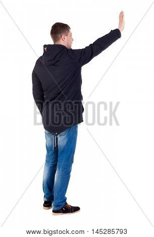 Back view of beautiful man welcomes. man hand waving from. Rear view people collection. Man in warm jacket waving his right hand in greeting to the left.