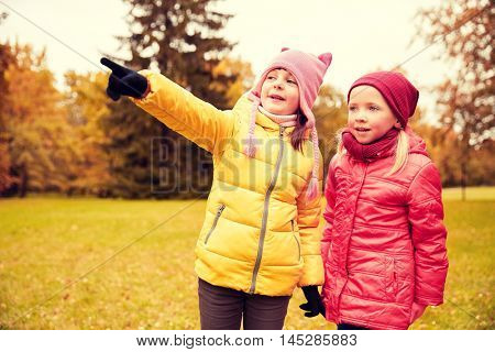 autumn, childhood, leisure, gesture and people concept - happy little girls pointing finger in park outdoors