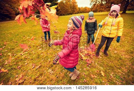 childhood, leisure, friendship and people concept - group of happy kids playing with and racking autumn maple leaves and having fun in park