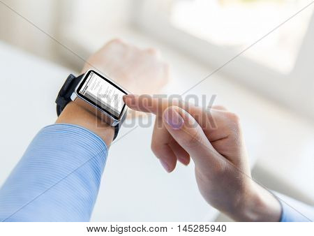 business, modern technology, programming and people concept - close up of female hands setting smart watch with coding on screen at office