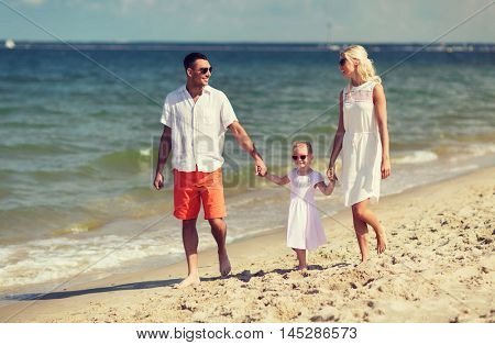 family, vacation, adoption and people concept - happy man, woman and little girl in sunglasses walking on summer beach