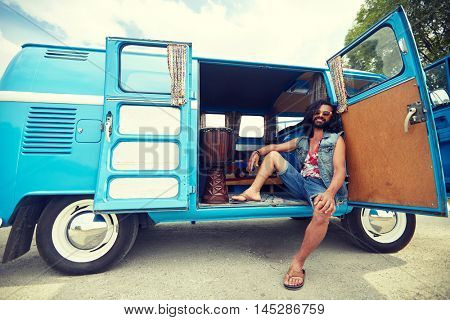 nature, summer, youth culture and people concept - smiling young hippie man with tom-tom drum in minivan car