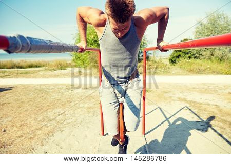 fitness, sport, exercising, training and lifestyle concept - young man doing triceps dip with weight belt on parallel bars outdoors