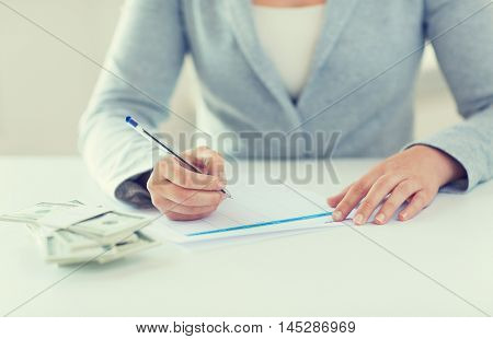 business, finance, tax and people concept - close up of woman hands with us dollar money filling tax paper form