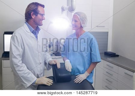 Smiling dentist talking to dental assistant in dental clinic