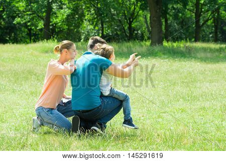 Woman Looking At Her Husband And Son Pointing At Something In The Park
