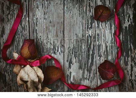 Dry red rose silk ribbon bow on old wooden table