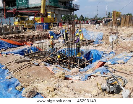MALACCA, MALAYSIA -OCTOBER 13, 2015: Construction workers fabricating steel reinforcement bar at the construction site in Malacca, Malaysia. The reinforcement bar was ties together using tiny cable.