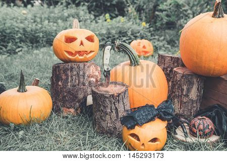 Halloween.  Jack-o-lantern. Scary Pumpkin With A Smile Near Knife In  Stump In Green Forest, Outdoor