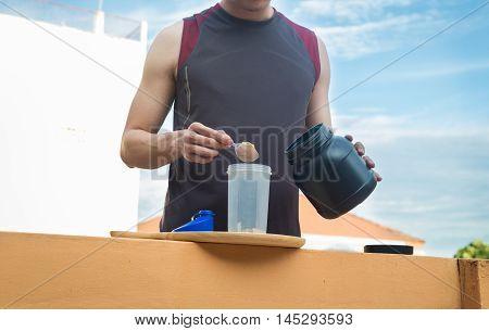 Whey protein healthy lifestyle man pour whey powder on the bottle.