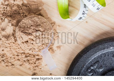 Scoop of whey protein on a wooden plate with measure tape. on top view