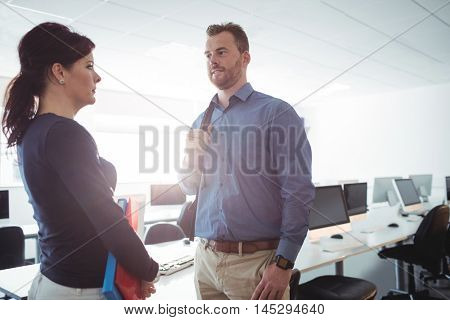 Mature students interacting with each other in the computer room at college
