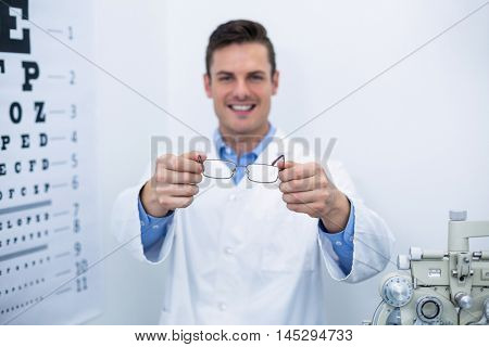 Smiling optometrist holding spectacles in ophthalmology clinic