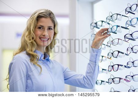 Smiling female customer selecting spectacles in optical store