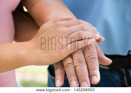 Close-up Of A Woman Holding Man's Hand