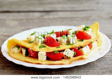 Delicious stuffed omelette on a plate isolated on old wooden background. Fried omelette stuffed with cheese, tomatoes and parsley. Eggs recipe. Closeup