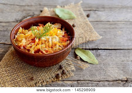 Braised cabbage in a clay bowl and on old wooden background. Cabbage braised with carrots, tomatoes and garlic and garnished with a sprig of dill. Vegetable diet dish