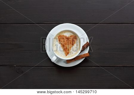 drawing a heart casting up cinnamon in a cup of cappuccino on dark wooden background top view / magic cinnamon sticks for a coffee