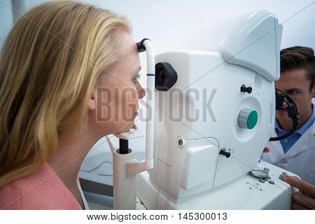Female patient looking through coreometry in ophthalmology clinic