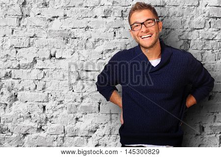Young man in a blue sweater and jeans smiles