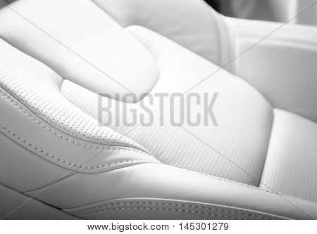 Modern car interior, driver seat white perforated leather
