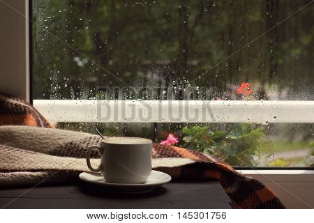 hot cup frothy coffee in the warm cozy home atmosphere / when behind a window passed a rain