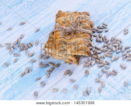 Cookies With Sunflower Seeds  Tied With String, Sunflower Seeds Scattered On Blue Wooden Table