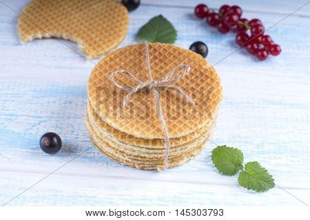 Stack of Dutch caramel waffles. Dutch waffle tied with string on wooden blue table.