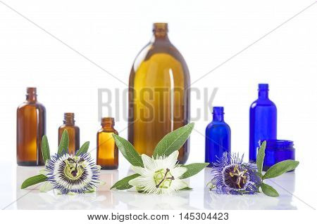 Passion flower with aromatherapy essential oil blue glass bottle isolated over white background.