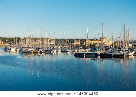 Sailing Yachts moored in Cardiff Cardiff Bay Wales United Kingdom. Photo taken in the golden hour.