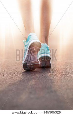 Woman feet running on road closeup on shoe.
