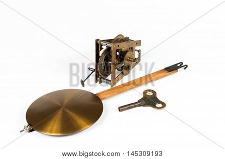 Old brass pendulum clock mechanism with a key and pendulum