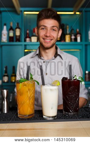 Young handsome Barman offers exotic sweet alcohol cocktails in night club. Professional male bartender at work in bar made drinks for party. Focused on glasses with straws